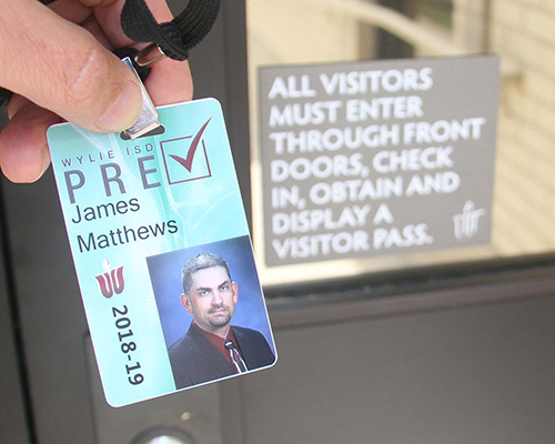 Wylie ISD Pre-Check ID card in front of entry security sign