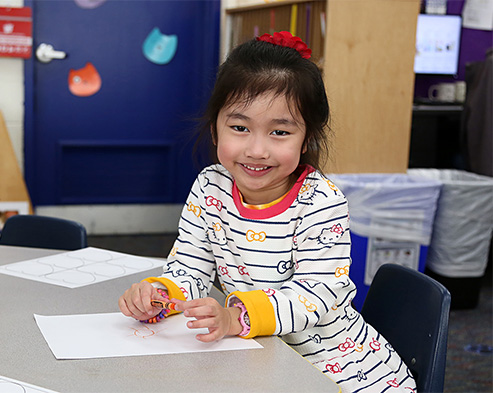 Female kindergartener smiling in a classroom.