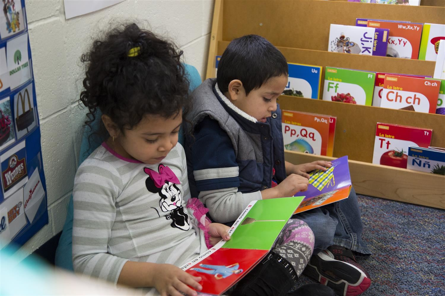 Two dual-language students reading books in classroom