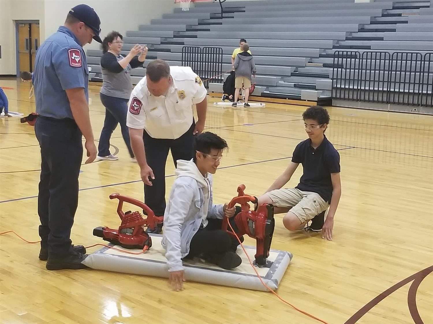 Fire department looking on as classmates test their hovercrafts